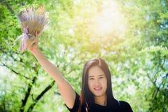 Mujeres asiáticas que sostienen el ramo de sonrisa de las flores Fotos de archivo libres de regalías
