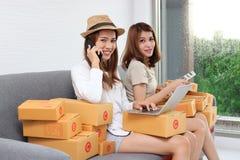 Mujeres asiáticas sonrientes del dueño del empresario con la caja de cartón que se sienta en el sofá moderno en casa En línea cre imagenes de archivo