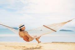 Mujeres asi?ticas que se relajan en vacaciones de verano de la hamaca en la playa foto de archivo