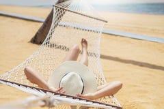 Mujeres asi?ticas que se relajan en vacaciones de verano de la hamaca en la playa imagenes de archivo
