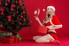 Mujeres atractivas en la ropa de Santa Claus cerca del árbol de navidad Imagen de archivo libre de regalías