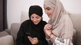 Mujeres atractivas en los hijabs que se sientan en el sofá gris mientras que mira smartphone junta en casa y la sonrisa Pared bla metrajes