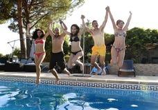 Mujeres atractivas felices jovenes de los hombres de los amigos en el bikini que salta en el aire a la piscina del hotel Imagen de archivo libre de regalías