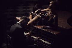 Mujeres atractivas que mienten en el piano Imagenes de archivo