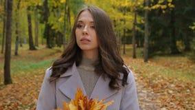 Mujeres bastante jovenes que esperan alguien en el parque del otoño plaing con sonrisa del ramo del mapleleaf alguien almacen de video