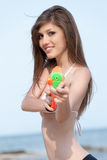 Mujeres bastante jovenes que juegan con el arma de agua en la playa Fotografía de archivo libre de regalías