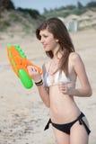 Mujeres bastante jovenes que juegan con el arma de agua en la playa Foto de archivo