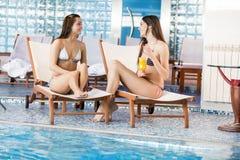 Mujeres jovenes que se relajan por la piscina Foto de archivo