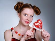 Mujeres bastante jovenes que sostienen el lollipop en forma de corazón Imágenes de archivo libres de regalías