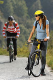 Mujeres biking en el camino Imagenes de archivo