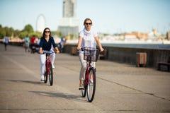 Mujeres biking en el embarcadero Imágenes de archivo libres de regalías