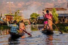Mujeres birmanas que reman en los barcos de madera, lago Inle, Myanmar Imagen de archivo