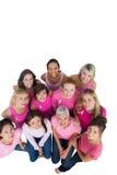 Mujeres bonitas alegres que miran el rosa para arriba que lleva para el cáncer de pecho Foto de archivo libre de regalías
