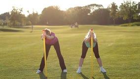 Mujeres bonitas del ajuste que hacen ejercicios con las barras de cuerpo almacen de metraje de vídeo