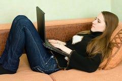Mujeres bonitas en el sofá usando el ordenador portátil Fotos de archivo libres de regalías