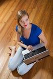 Mujeres bonitas en suelo de madera usando una computadora portátil Imagenes de archivo
