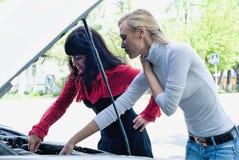 Mujeres bonitas jovenes en el coche quebrado Imágenes de archivo libres de regalías