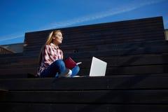 Mujeres bonitas jovenes que trabajan en el red-libro mientras que se relaja en el aire fresco Foto de archivo libre de regalías