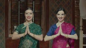 Mujeres bonitas que conectan las manos en el saludo del namaste almacen de video
