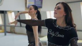 Mujeres bonitas que hacen los movimientos ondulados de brazos en una danza de vientre almacen de metraje de vídeo