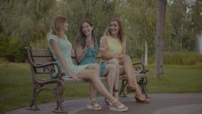 Mujeres bonitas que se sientan y que cotillean en banco en parque metrajes