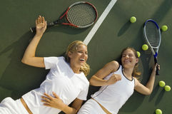 Mujeres cansadas felices que ríen en campo de tenis fotografía de archivo libre de regalías