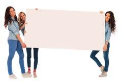 3 mujeres casuales felices que presentan a un tablero en blanco grande Fotografía de archivo