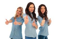 3 mujeres casuales jovenes que hacen la autorización manosean con los dedos encima de muestra Fotografía de archivo libre de regalías