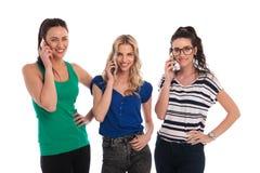 Mujeres casuales jovenes sonrientes que hablan en los teléfonos móviles Imágenes de archivo libres de regalías