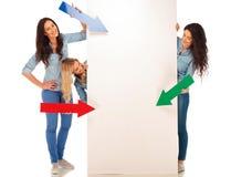 3 mujeres casuales que señalan flechas coloreadas a una cartelera en blanco Imagenes de archivo