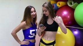 Mujeres caucásicas alegres jovenes que escuchan la música en un club de fitness metrajes