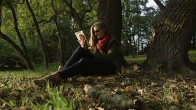 Mujeres caucásicas jovenes hermosas en gafas de sol usando la tableta en el parque almacen de video