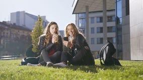 Mujeres caucásicas jovenes que beben el jugo fresco mientras que se sienta en la hierba verde usando el teléfono móvil que toma l almacen de video