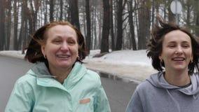 Mujeres cauc?sicas mayores y jovenes felices que corren en el parque nevoso en el invierno que habla y que sonr?e Cerca francamen metrajes