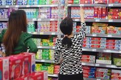 Mujeres chinas en las alamedas de compras para comprar crema dental Foto de archivo libre de regalías
