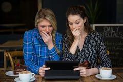 Mujeres chocadas que usan la tableta en cafetería imagenes de archivo