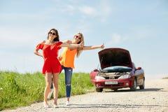 Mujeres con el coche quebrado que hacen autostop en el campo Imágenes de archivo libres de regalías