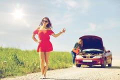 Mujeres con el coche quebrado que hacen autostop en el campo Foto de archivo libre de regalías