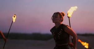 Mujeres con el fuego en la puesta del sol en los trucos de la danza y de la demostración de la arena contra el cielo hermoso en l almacen de video