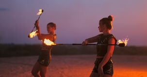 Mujeres con el fuego en la puesta del sol en los trucos de la danza y de la demostración de la arena contra el cielo hermoso en l almacen de metraje de vídeo