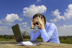 Mujeres con el ordenador portátil, sentándose en el jardín, llevando a cabo su cabeza debido a problemas en el trabajo Foto de archivo libre de regalías