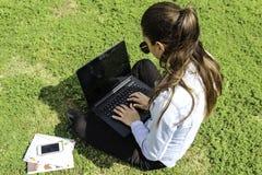 mujeres con el ordenador portátil, sentándose en el jardín que trabaja con un ordenador portátil Fotos de archivo libres de regalías