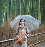 Mujeres con el paraguas en el bosque de bambú imagenes de archivo