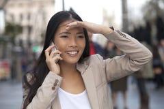 Mujeres con el teléfono celular que mira alguien Fotografía de archivo