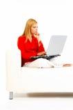 Mujeres con la computadora portátil en el sofá Foto de archivo