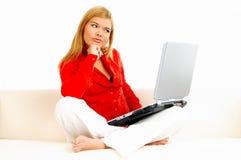Mujeres con la computadora portátil en el sofá Imágenes de archivo libres de regalías