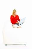Mujeres con la computadora portátil en el sofá Imagen de archivo