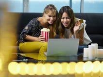 Mujeres con la PC del ordenador portátil que hace una oferta en la subasta en línea Foto de archivo