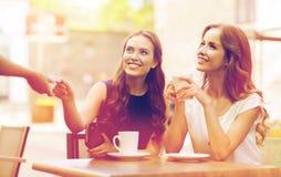 Mujeres con la tarjeta de crédito que paga el café en el café Fotografía de archivo