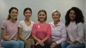 Mujeres con las cintas del rosa enteradas de cáncer de pecho, sonriendo en cámara, salud almacen de metraje de vídeo